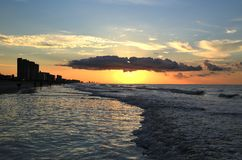 Les vagues de mer miroitent au-dessous du Soleil Levant sur le rivage côtier d'océan Images libres de droits