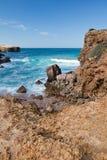 Les vagues de rupture contre des roches en turquoise arrosent sur le fond de l'Océan Atlantique Images stock