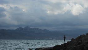 Les vagues de Time Lapse frappent le rivage et les élever d'homme aux cieux obscurcis de pierres se déplacent à la visionneuse de clips vidéos