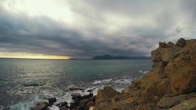 Les vagues de Timelapse frappent le rivage en pierre et les cieux obscurcis se déplacent à la visionneuse devant des roches et de clips vidéos