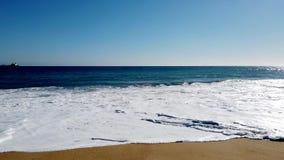 Les vagues enroulent à la plage avec le cargo dans la distance banque de vidéos