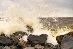 Les vagues ont battu contre les roches sur la création de bord de mer éclabousse images libres de droits