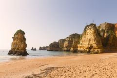 Les vagues roulent sur une plage sablonneuse pendant la marée basse dans Algarve, Portugal Photos libres de droits