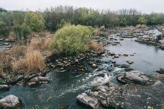 Les vagues rugueuses d'écoulement d'eau de courant de montagne aménagent des pierres en parc photo stock