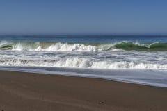 Les vagues se brisant sur une plage sablonneuse faisant la mer écument Photos libres de droits