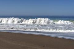 Les vagues se brisant sur une plage sablonneuse faisant la mer écument Photo libre de droits
