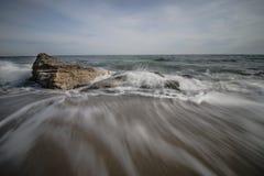 Les vagues se brisent dans des roches sur la plage Image libre de droits