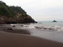 Les vagues se brisent sur la plage foncée de sable à Manzanillo, Mexique images stock