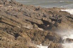 Les vagues se cassant au-dessus des roches près marmonne, le Pays de Galles, R-U Images stock
