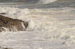 Les vagues se cassant au-dessus des roches près marmonne, le Pays de Galles, R-U Photos stock