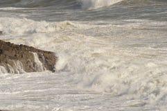 Les vagues se cassant au-dessus des roches près marmonne, le Pays de Galles, R-U Photographie stock libre de droits