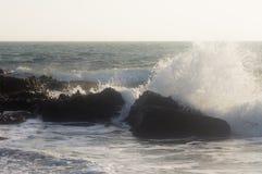 Les vagues se cassent au sujet des roches dans l'eau près du rivage Images stock