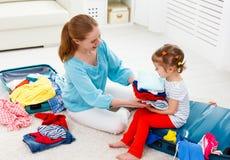 Les valises heureuses de fille de mère et d'enfant de famille ont emballé pour le vaca Photos stock