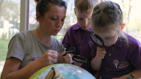 Les van aardrijkskunde, leerlingen en jonge leraar die met vergrootglas de bol in kleuterschool bestuderen stock footage