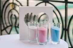 Les vases en verre avec le sable et le cadre de couleur aiment le coeur Photo stock
