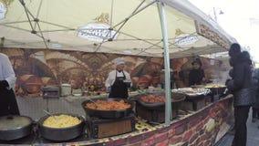 Les vendeurs de cuisinier vendent la nourriture chaude nouvellement préparée dans le festival extérieur banque de vidéos