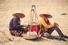 Les vendeuses de femmes dans des chapeaux s'asseyent et se reposent sur la plage de sable au Vietnam Photographie stock libre de droits