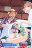 Les ventes des exploitants mûres heureuses ses légumes organiques frais dans un marché images stock