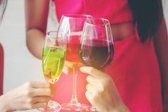 Les verres avec des cocktails se sont tenus par les amis heureux à la partie, le meilleur frie Photographie stock libre de droits