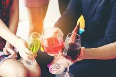 Les verres avec des cocktails se sont tenus par les amis heureux à la partie, le meilleur frie Photos libres de droits
