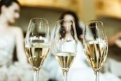 Les verres avec le champagne se tiennent sur la table dans l'avant de la jeune mariée Image stock