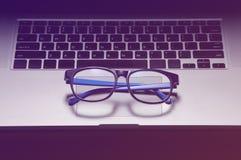Les verres bleus sur l'ordinateur portable, clôturent - le concept du repos de l'effort a photos stock