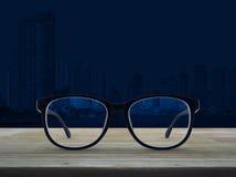 Les verres d'oeil au beurre noir sur la table en bois au-dessus de la ville moderne de bureau dominent Photos stock
