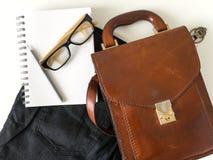 Les verres d'oeil de carnet crayonnent et le sac en cuir sur le fond blanc Photo libre de droits