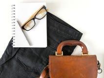 Les verres d'oeil de carnet crayonnent et le sac en cuir sur le fond blanc image libre de droits