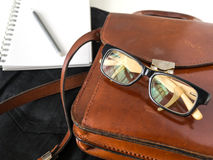 Les verres d'oeil de carnet crayonnent et le sac en cuir sur le fond blanc Images stock