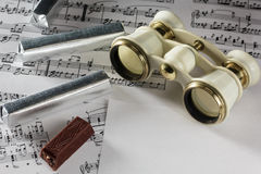 Les verres d'opéra antiques reposent sur les notes musicales Photographie stock libre de droits