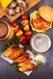 Les verres de bière avec des ailes de poulet, hamburger, boules de viande, ont grillé le maïs et des légumes Morsures de bière Images stock