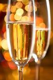 Les verres de Champagne ont tiré contre les lumières de scintillement d'arbre de Noël Photos stock