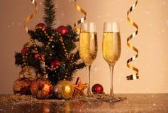 Les verres de champagne sur le fond de Noël avec le vol neigent Photo stock