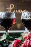 Les verres de la Saint-Valentin wine avec les lettres AIMENT, des fleurs et des coeurs Photos libres de droits