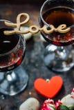 Les verres de la Saint-Valentin wine avec les lettres AIMENT, des fleurs et des coeurs Photographie stock libre de droits