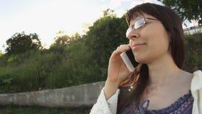 Les verres de port de jeune femme et un blanc ont tricoté la veste parlant au téléphone clips vidéos