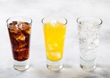 Les verres de soude boivent avec des glaçons et des bulles sur le fond en pierre de table de cuisine Kola et soude orange de limo images libres de droits