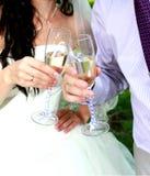 Les verres de tintement de jeunes mariés Photo stock