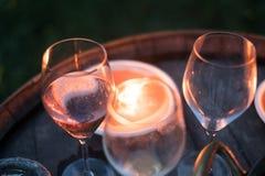 Les verres de vin illuminés par nuit de bougies font la fête Photos stock