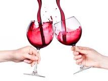 Les verres de vin rouge avec éclabousse à disposition d'isolement Images stock