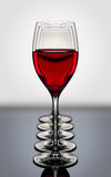 Les verres de vin rouge dans une rangée ont éclairé à contre-jour sur un verrat noir réfléchissant Images stock