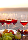 Les verres du vin rouge sur le coucher du soleil échouent Photos libres de droits