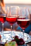 Les verres du vin rouge sur le coucher du soleil échouent Photographie stock libre de droits