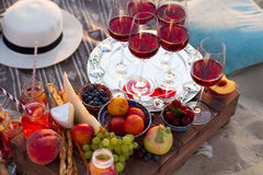 Les verres du vin rouge sur le coucher du soleil échouent Photo stock