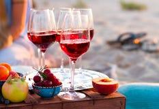 Les verres du vin rouge sur le coucher du soleil échouent Photographie stock