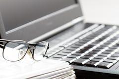 Les verres et l'ordinateur portable sur l'espace de travail soustraient le fond de comptabilité d'entreprise Photographie stock