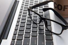 Les verres et le stylo de l'homme d'affaires sur l'ordinateur portable Photos stock