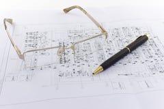 Les verres et le stylo se trouvent sur le dessin industriel Photo stock