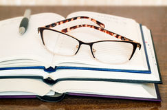 Les verres, les livres et le carnet sur la table apprêtent Photos libres de droits